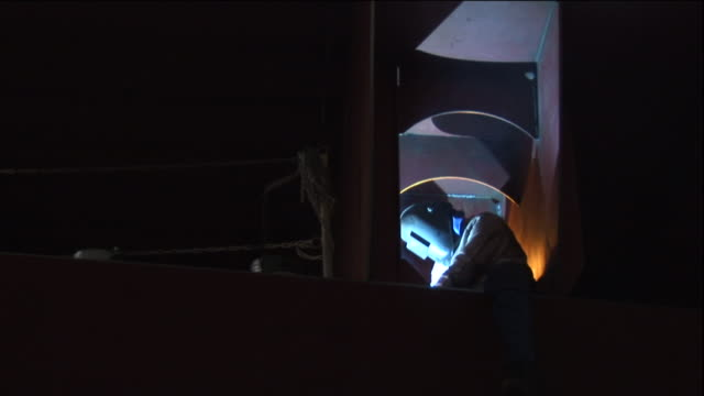 a blue light illuminates the face of a welder as he works. - welding helmet stock videos & royalty-free footage
