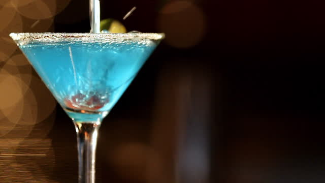 A blue martini splashes over a cherry in a glass.