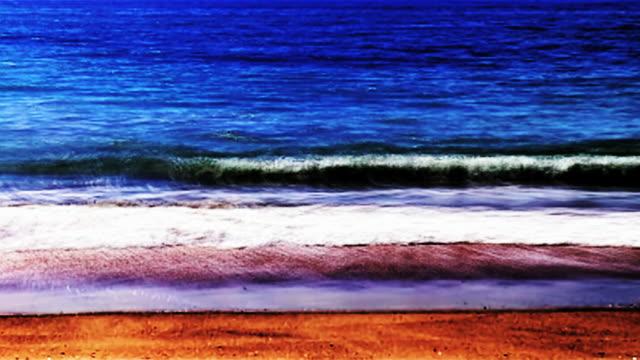 blue ocean waves roll onto a golden beach. - digitale verbesserung stock-videos und b-roll-filmmaterial