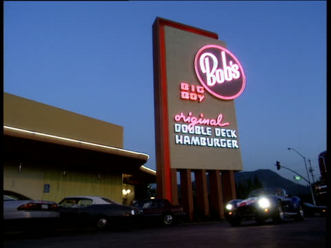 stockvideo's en b-roll-footage met blue open topped car drives though american diner. neon hamburger sign in background los angles - westelijke verenigde staten