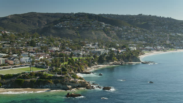 blue pacific waves lapping against the coast with houses reaching up the hillside in laguna beach - laguna beach california stock videos & royalty-free footage