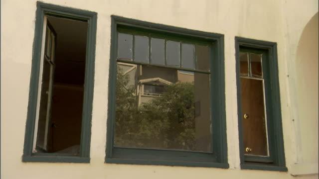 vídeos de stock, filmes e b-roll de blue paint covers the frames of old windows on a house. - armação de janela