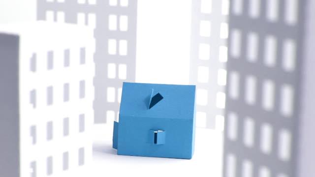 vidéos et rushes de bleu maison de papier entre les bâtiments blancs - objet en papier
