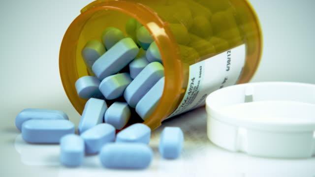 Blue pills in an open prescription bottle.