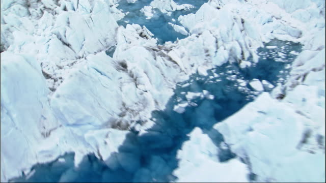blue pools of frozen water surround jagged peaks of ice on columbia glacier alaska. available in hd. - columbia glacier stock videos & royalty-free footage
