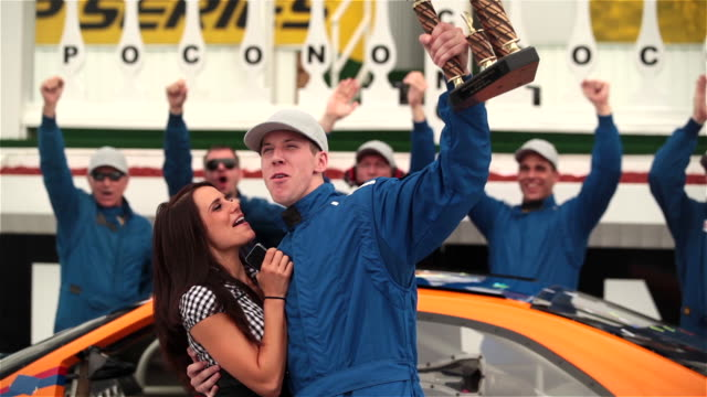 Blue racing team waves checkered flag and celebrates stock car victory at motor speedway.