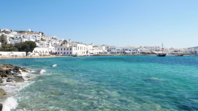 blue sea with town of chora on mykonos greece, 4k resolution. - mykonos stock videos & royalty-free footage