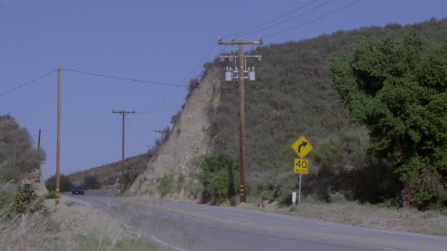 ts a blue sedan driving swiftly down mountainside road / los angeles, california, united states - formato panoramico con bande nere video stock e b–roll