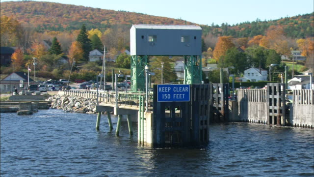 blue sign keep clear 150 feet on dock in docking area off coast of island trees houses hills bg - augusta maine stock videos & royalty-free footage