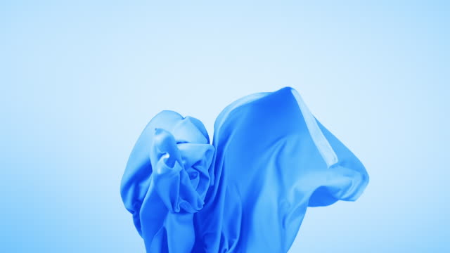 vídeos de stock, filmes e b-roll de blue silky fabric flowing by wind in blue background, slow motion - material têxtil