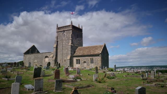 Blue skies and white clouds pass the Old Church of St Nicholas Uphill Somerset