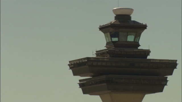 blue skies create a backdrop for an airport's control tower. - torre di controllo video stock e b–roll