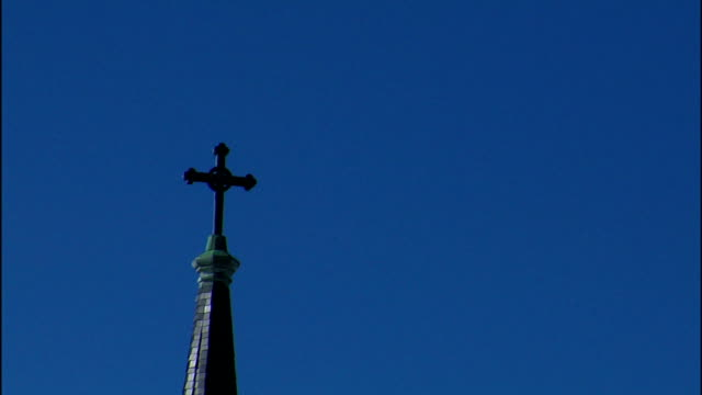 blue skies provide a backdrop for a cross on a spire. - spire stock videos & royalty-free footage