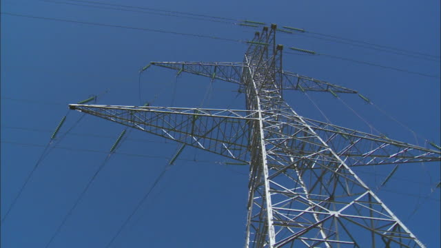 Blue skies surround an electricity pylon.