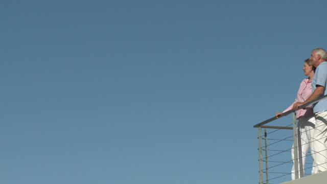 blue sky and couple standing on balcony - 2人点の映像素材/bロール