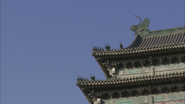 A blue sky outlines a pagoda roof with a dragon motif in Beijing, China.