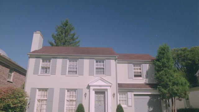 a blue sky spreads above a pristine two-story white house. - zweistöckiges wohnhaus stock-videos und b-roll-filmmaterial