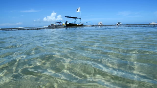 blue sky with dragonfly  boat on the beach. Jukung fishing boats on Sanur beach, Bali, Indonesia, Asia