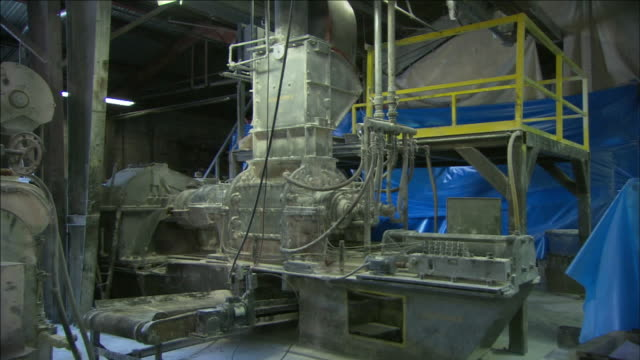 blue tarps cover some manufacturing equipment in a production area. - 防水シート点の映像素材/bロール