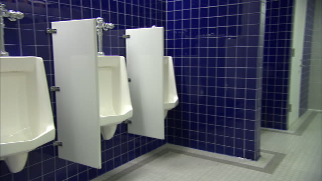 blue tiled walls border urinals and stalls in a public restroom. - urinal stock videos & royalty-free footage