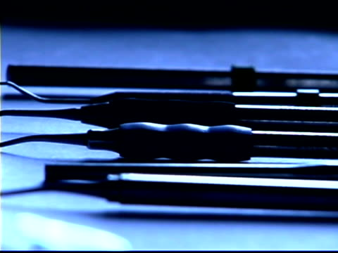 vidéos et rushes de blue tone close-up pan right of dental instruments on a metal tray; slight rack focus. - groupe moyen d'objets