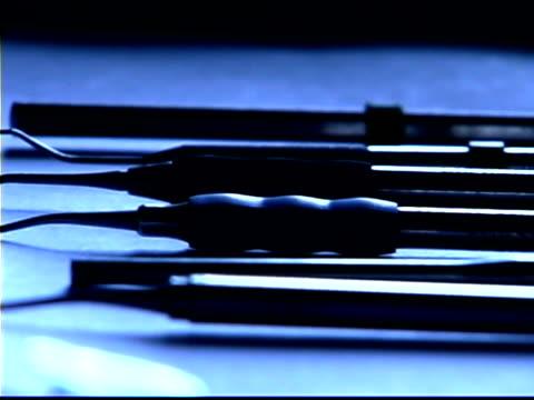 blue tone close-up pan right of dental instruments on a metal tray; slight rack focus. - einige gegenstände mittelgroße ansammlung stock-videos und b-roll-filmmaterial