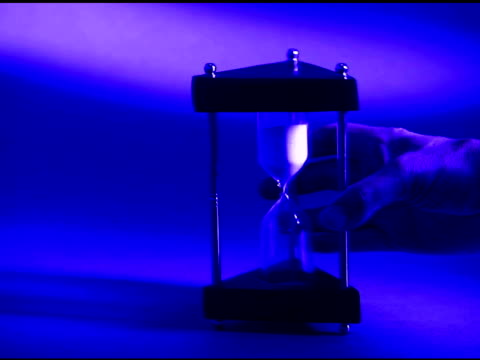 blue tone of a man¿s hand turning an hourglass over. - tungsten image stock videos and b-roll footage