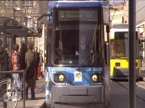 blue tram pulls away from tram stop towards camera pedestrians cross busy street berlin - tram stock-videos und b-roll-filmmaterial