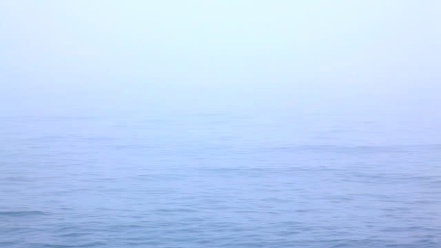 Blue tranquil sea background in the fog