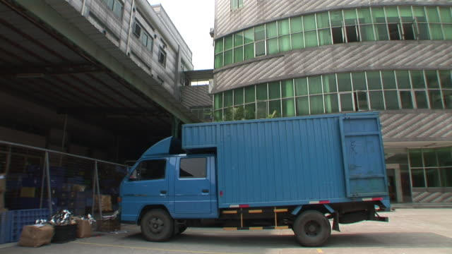 WS, PAN, Blue truck parked in front of industrial building, Dongguan City, China