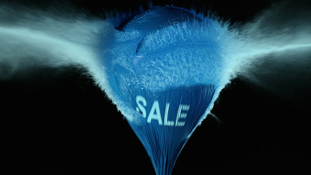 SLO MO blue water filled balloon with sale sign exploding