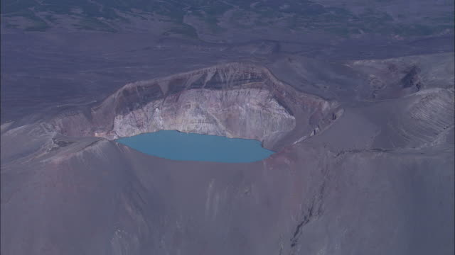 Blue water fills a volcanic crater.
