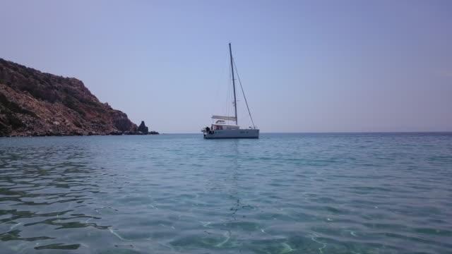 blauwasser schwankt segelboot in abgelegenen bucht verankert - anchored stock-videos und b-roll-filmmaterial