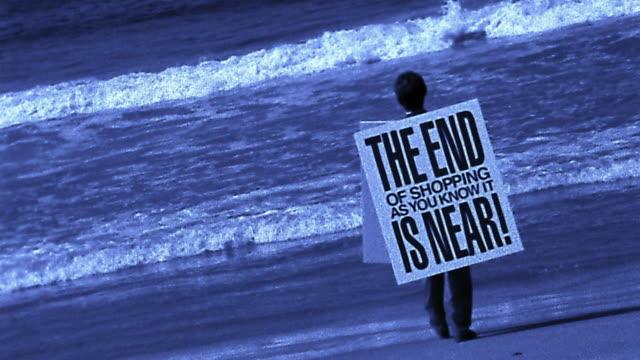 Blue wide shot man in sandwich board sign: 'End (of shopping) is Near' walking into ocean
