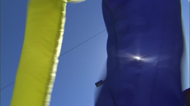 vídeos de stock, filmes e b-roll de blue yellow inflated flailingarm air dancer tube man blowing in the wind under blue sky with bright muted sun god rays - enchendo