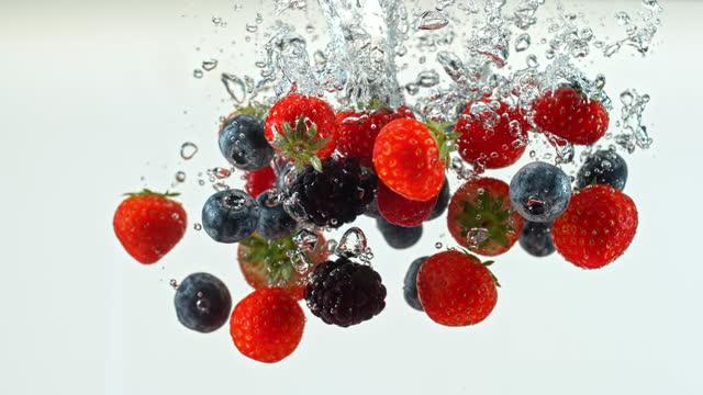 slo mo ld mirtilli, fragole e more che cadono in acqua - antiossidante video stock e b–roll