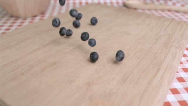 stockvideo's en b-roll-footage met blueberry falling in super slow motion on a wood board - tafelkleed