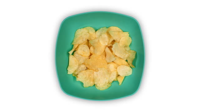 a blue-green dish filling with potato chips and emptying again, time lapse - salty snack stock videos & royalty-free footage