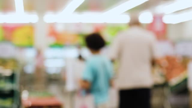 stockvideo's en b-roll-footage met onscherpte achtergrondgroep mensen die vers voedsel van plank bij supermarkt kopen - dairy product