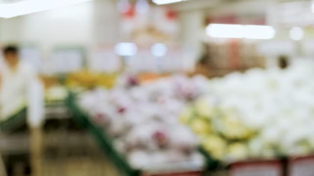 vidéos et rushes de groupe de fond flou de personnes achetant la nourriture fraîche de l'étagère au supermarché - panier courses