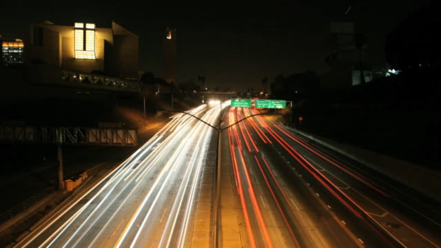 vidéos et rushes de blur of traffic lights moving in both directions on highway below. ca - phare de véhicule