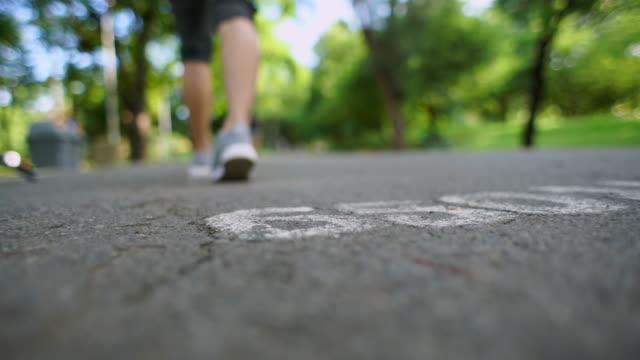 vídeos de stock e filmes b-roll de blur sport woman walk and stretching in park - distante