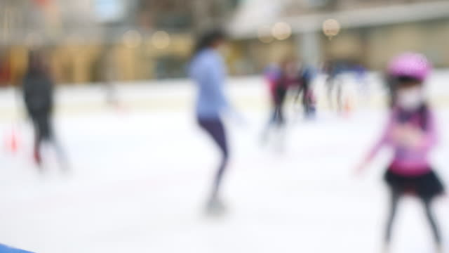 blured or out of focus people ice skating at sports stadium and bokeh. for backgrounds - ice rink stock videos & royalty-free footage