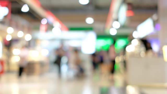 blurred background of shopping mall with customer walking in front of  store with bokeh light. - department store stock videos & royalty-free footage