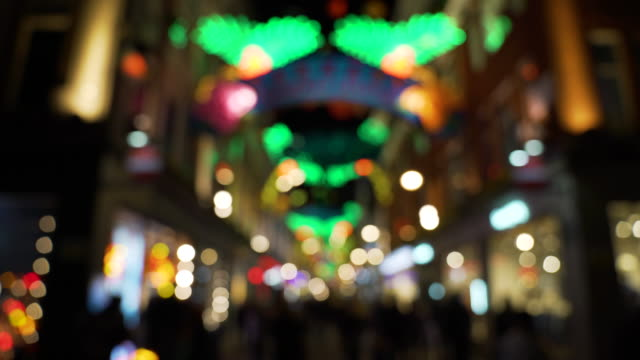 Blurred lights come into focus to reveal Carnaby Street with carnival style Christmas decorations