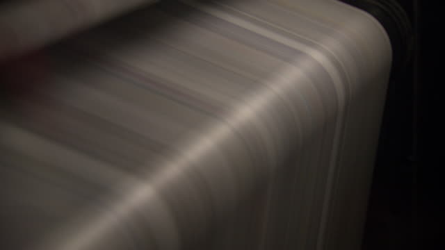 blurred motion creates a stripy effect on newspaper running through a printing press, uk. - folded paper stock videos and b-roll footage