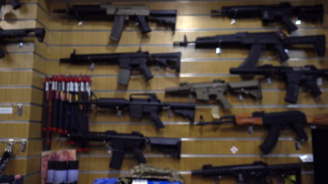 blurred motion, gun shop and/or bb gun shop. - arma da fuoco video stock e b–roll