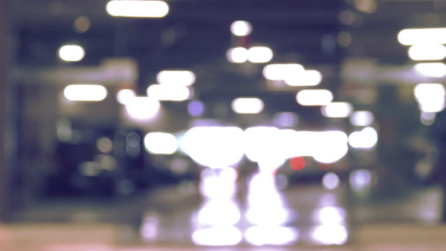 blurred motion of parking lot in building and people shopping mall. - parcheggio video stock e b–roll