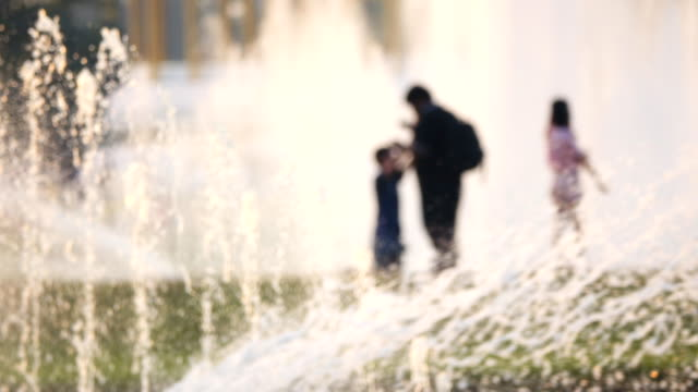 Suddig rörelse av folk och vatten fontän i park bangkok