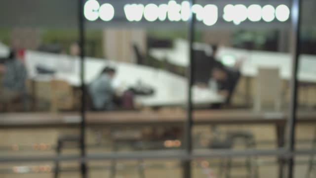 vidéos et rushes de floue personnes travaillant à l'espace de travail central nuit - espace texte